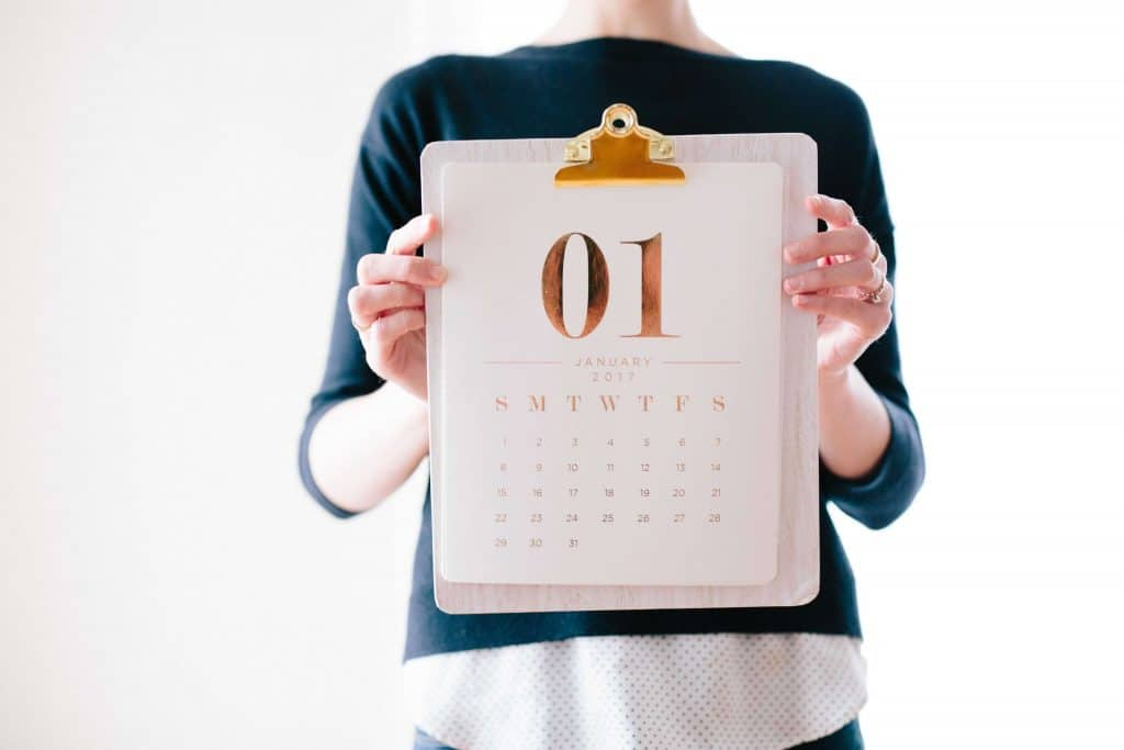 Woman holding up a calendar on a clipboard